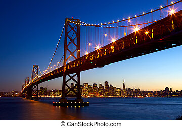 San Francisco skyline and Bay Bridge at sunset, California, ...