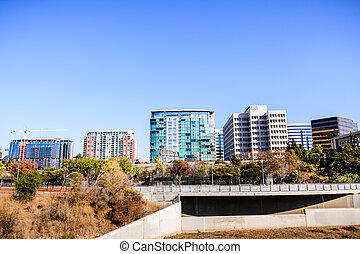 San Jose's downtown skyline as seen from the shoreline of Guadalupe river on a sunny fall day; Silicon Valley, California