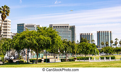 San Jose's downtown skyline as seen from the shoreline of Guadalupe River Park on a sunny spring day; Silicon Valley, California