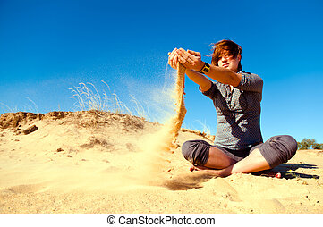 Woman playing with sand and wind