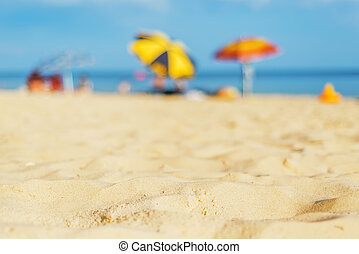 sand beach closeup with umbrellas near sea. soft focus on bottom of the picture