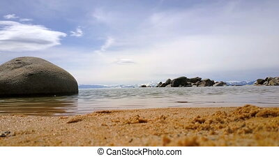 Sand beach of Lake Tahoe, big boulder in water and mountains...
