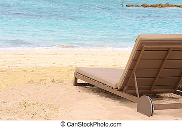 Sand beach with parasol and Sunbeds.