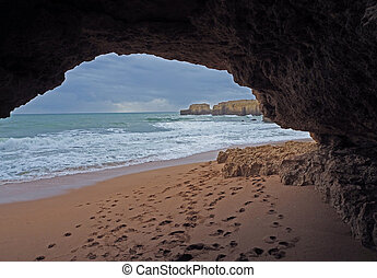 sand beach with sandstone window and foot prints and cliffs