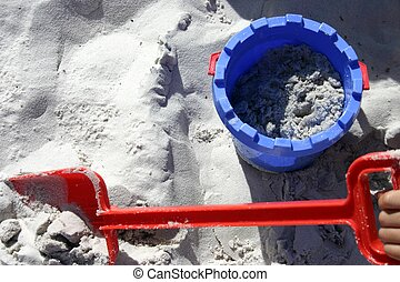 Sand Bucket n Spade - Blue and red, bucket and spade in sand...
