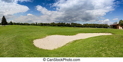 Sand bunker on golf course with perfect green grass
