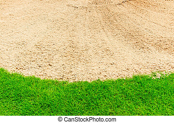 Sand bunker on the beautiful golf course and green grass