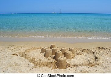 A sand castle on a sunny beach and calm clear sea water. Shot taken in Sardina, Italy.