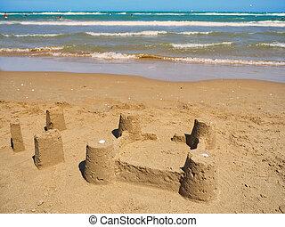 Sand castle or sandcastle on the beach at sea