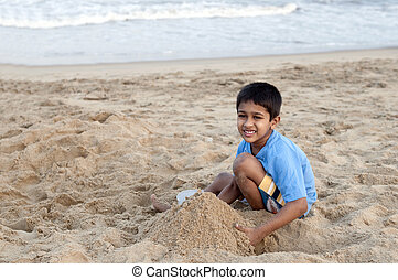 Sand Castle - an handsome young indian kid building sand...