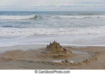 Sand castle surrounded by a moat on the beach.