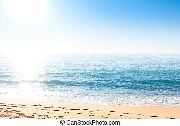 Sand coastline against bright shining sun