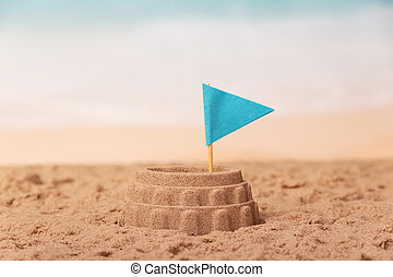 Sand colosseum with flag close up on background of sea.