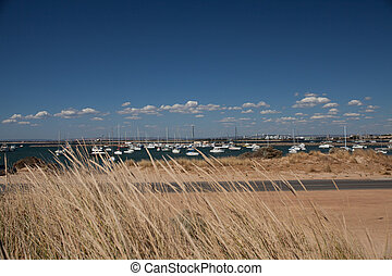 Sand dunes and a street in front of a harbor with yachts under blue sky wiith little withe clouds