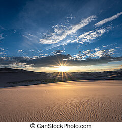 Sand Dunes Ripple Below Sun Burst from sunset