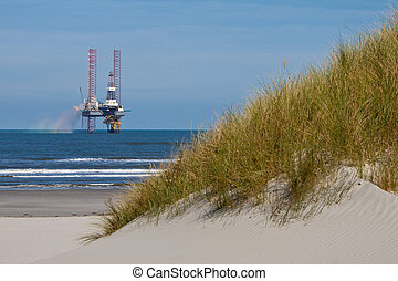 Sand dunes with beach grass and a drilling platform in the ocean