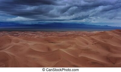 Sand dunes with storm clouds at sunset in desert