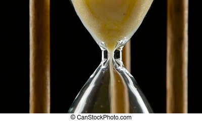 Sand falls through a bottleneck in a hourglass. Black. Close...