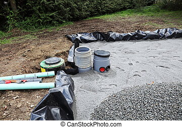 Installing a sand and gravel filter for a domestic sewage system showing the underlying coarse sand and gravel which will be used to cover it once the upper layer of pipes has been installed .