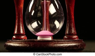 Sand flowing in hourglass. Black. Slow motion. Close up -...