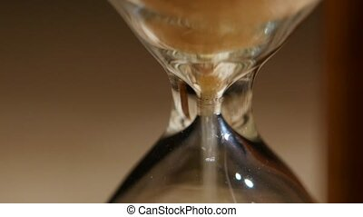 Sand flowing through an hourglass. Close up - Yellow sand...