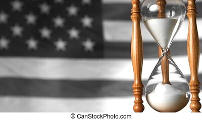 Sand flowing through hourglass with american flag waving in...