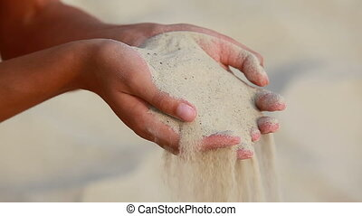 Human hands strewing sand through fingers