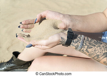 Sand is poured through female hands
