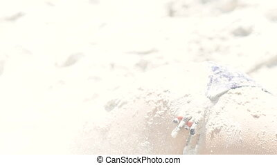 Sand is pouring on the bare body of woman. Slow motion