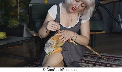 Sand Lizard on a female hand. A blonde woman stroking her home iguana lizard, the girl smiles and looks at the camera.