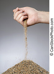 Man adding sand in a heap with his hand