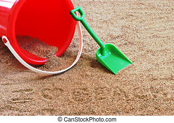 Sand Pail and Shovel - A red sand pail and shovel at th...