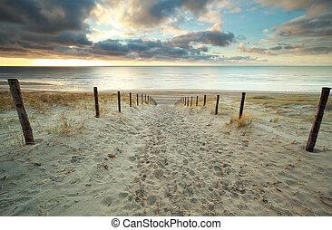 sand path to North sea beach at sundown