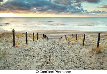 sand path to the North sea at sunset