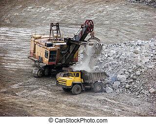 sand-pit - Ekskavator loads a stone on a truck...