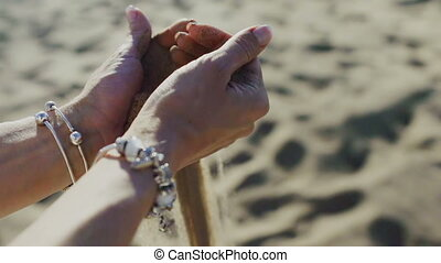 Sand pours through the hands of women on beach