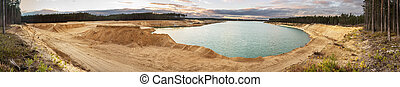 Sand quarry with blue lake under the magnificient sky. Big panorama 88 megapixels, 21.957x4000px.