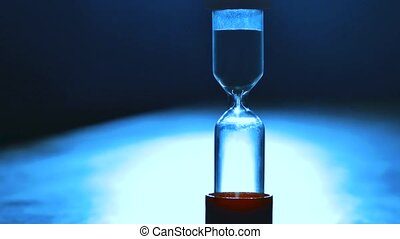 Sand running through the bulbs of an hourglass measuring the passing time in a countdown to a deadline. Closeup hourglass clock on light blue background concept lifestyle