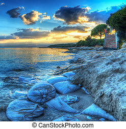 sand sacks on the shore at sunset in Alghero