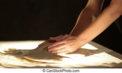 Sand spilling out of female hands close-up