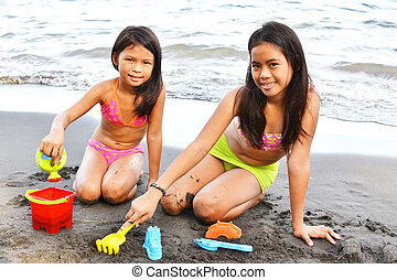 Sand Toys - Two little sisters playing on the beach with...
