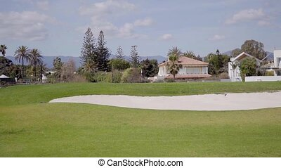 Sand trap and green golf course near houses - Sand trap and...