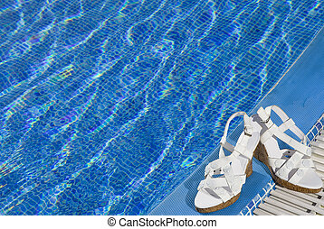 sandal lies on the brink of pool