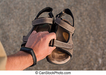 sandals in the hand of a man on the beach