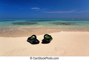 sandals on sand against the ocean