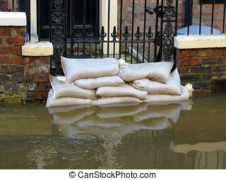 York flooded street - Sandbags stacked in front of house in...
