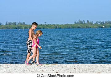 Sandbar beach walk - Boy and girl walking on sandbar beach