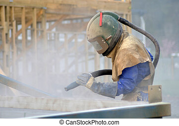 tradesman sandblasting beams for building project