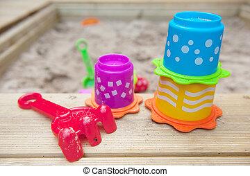 sandbox with plastic toys form wood