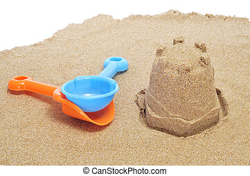 a sandcastle on the sand and each shovels